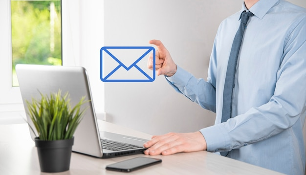 Icona dell'e-mail della tenuta della mano dell'uomo d'affari, contattaci tramite e-mail di newsletter e proteggi le tue informazioni personali dalla posta indesiderata. call center del servizio clienti contattaci concetto