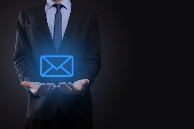 Mano dell'uomo d'affari che tiene l'icona di posta elettronica, contattaci tramite e-mail di newsletter e proteggi le tue informazioni personali dalla posta spam. il call center del servizio clienti contattaci concetto.