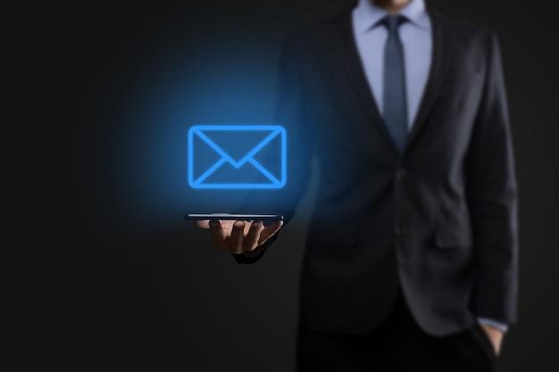 Mano dell'uomo d'affari che tiene l'icona di posta elettronica, contattaci tramite e-mail di newsletter e proteggi le tue informazioni personali dalla posta indesiderata. il call center del servizio clienti contattaci concetto.