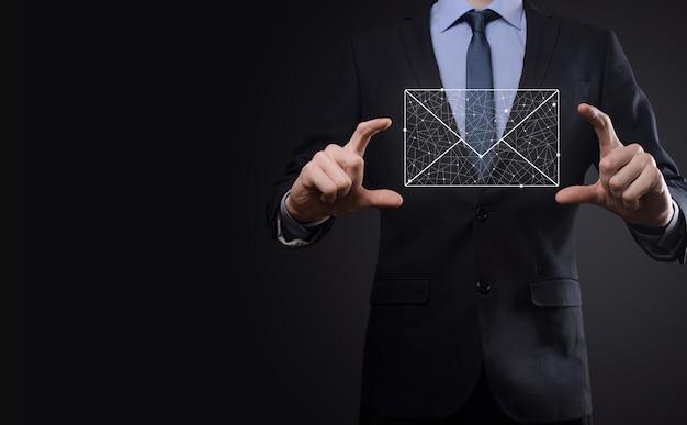 Icona della posta elettronica della tenuta della mano dell'uomo d'affari, contattaci tramite e-mail di newsletter e proteggi le tue informazioni personali dalla posta spam il call center del servizio clienti contattaci concetto.