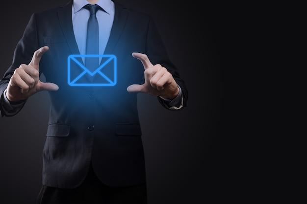 Icona dell'e-mail della tenuta della mano dell'uomo d'affari, contattaci tramite e-mail di newsletter e proteggi le tue informazioni personali dalla posta indesiderata. il call center del servizio clienti contattaci concetto.