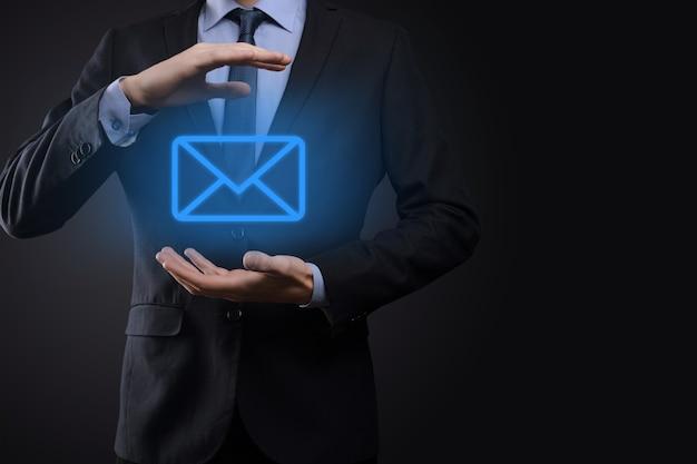 Mano dell'uomo d'affari che tiene l'icona di posta elettronica, contattaci tramite e-mail di newsletter e proteggi le tue informazioni personali dalla posta indesiderata