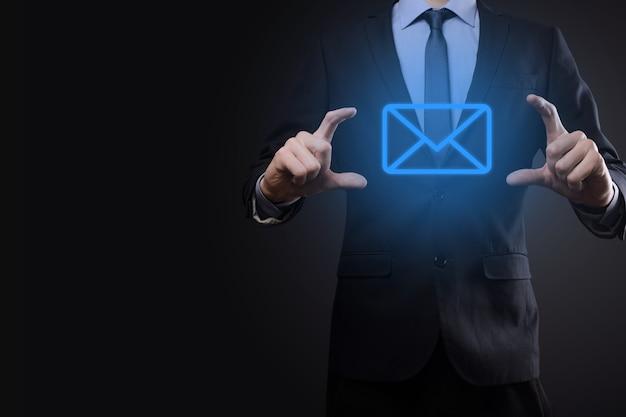 Mano dell'uomo d'affari che tiene l'icona di posta elettronica, contattaci tramite email di newsletter e proteggi le tue informazioni personali