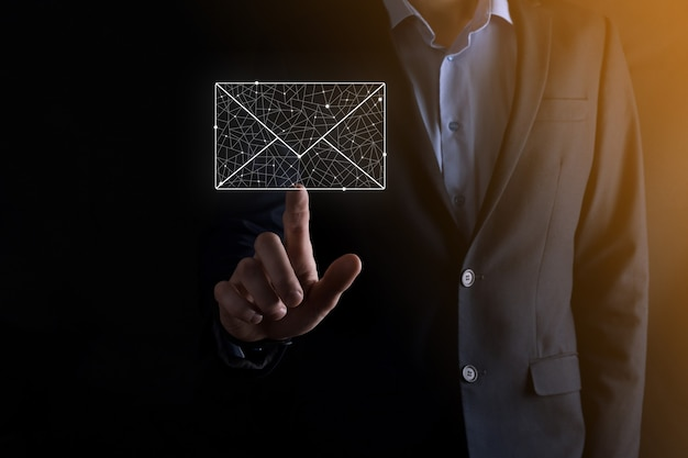 Mano di uomo d'affari che tiene l'icona di posta elettronica