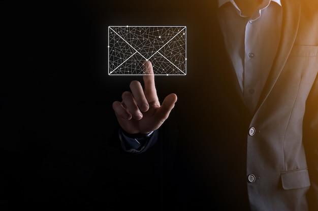 Mano dell'uomo d'affari che tiene l'icona dell'e-mail, contattaci tramite e-mail della newsletter e proteggi le tue informazioni personali dalla posta spam