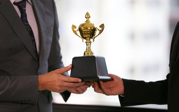 Mano di uomo d'affari che tiene trofeo d'oro, premio vincitore di affari.