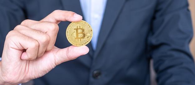 Mano dell'uomo d'affari che tiene la criptovaluta bitcoin dorato (btc), crypto è denaro digitale all'interno della rete blockchain, viene scambiato utilizzando la tecnologia e lo scambio internet online. concetto finanziario