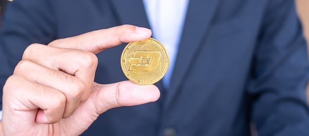 La mano dell'uomo d'affari che tiene la moneta di criptovaluta dash dorata, crypto è denaro digitale all'interno della rete blockchain, viene scambiata utilizzando la tecnologia e lo scambio internet online. concetto finanziario