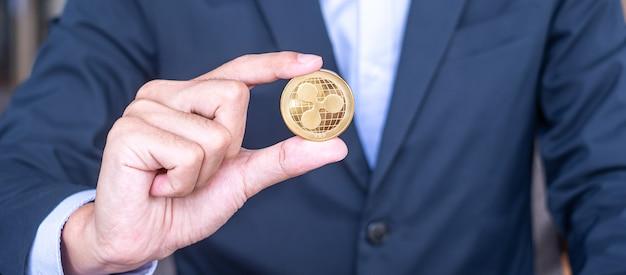 Mano dell'uomo d'affari che tiene la moneta di criptovaluta dorata ripple (xrp), crypto è denaro digitale all'interno della rete blockchain, viene scambiata utilizzando la tecnologia e lo scambio internet online. concetto finanziario