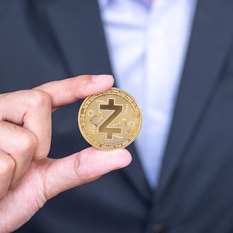 La mano dell'uomo d'affari che tiene la moneta di criptovaluta zcash (zec) dorata, crypto è denaro digitale all'interno della rete blockchain, viene scambiata utilizzando la tecnologia e lo scambio internet online. concetto finanziario