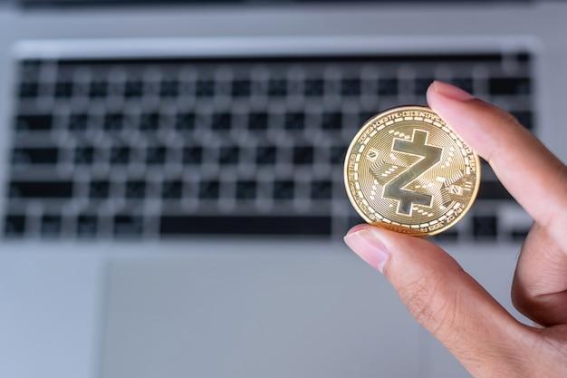 Mano dell'uomo d'affari che tiene la moneta di criptovaluta golden zcash (zec) sulla tastiera del laptop, crypto è denaro digitale all'interno della rete blockchain, utilizza la tecnologia e lo scambio internet online.