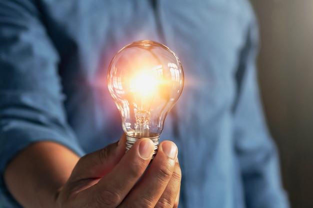 Lampadina della tenuta della mano dell'uomo d'affari. idea energia elettrica a risparmio energetico alternativo