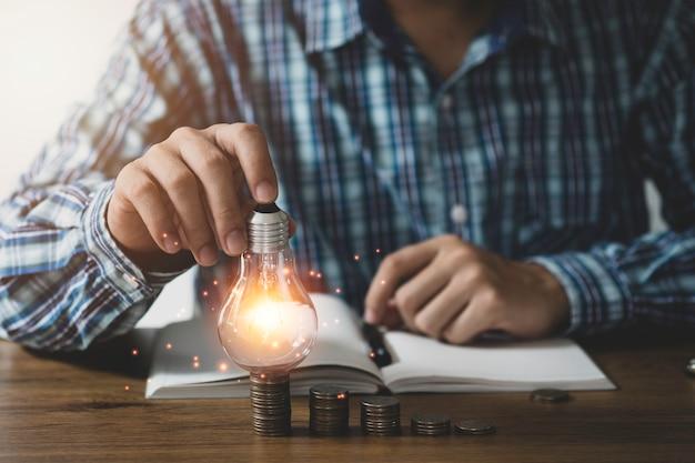 Lampadina della tenuta della mano dell'uomo d'affari con l'ingranaggio del dente e la linea di collegamento. concetto di idea di pensiero creativo.