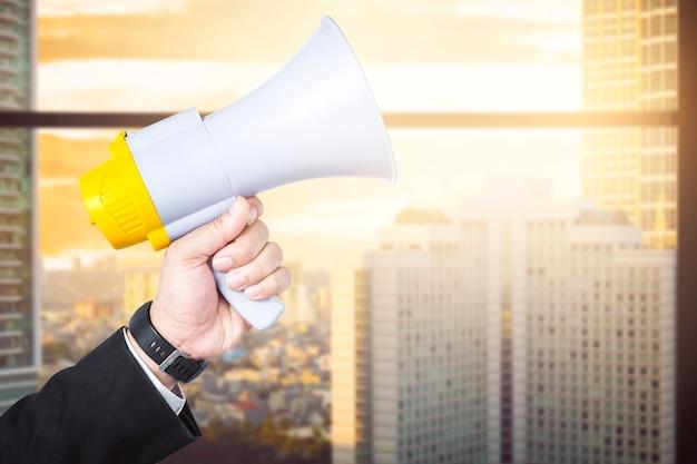 Mano di uomo d'affari che tiene il megafono con sfondo edificio per uffici