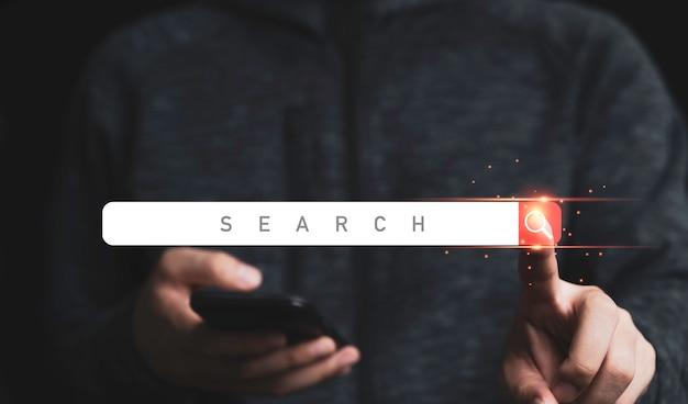 Mano dell'uomo d'affari che tiene il telefono cellulare e tocca un design digitale di un'icona della barra di ricerca