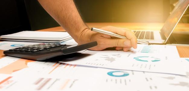 Mano dell'uomo d'affari che tiene una penna con calcolatrice, scartoffie e laptop sul tavolo nella sala riunioni