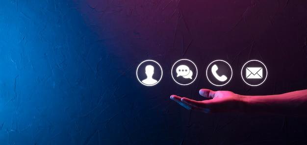 Mano dell'uomo d'affari che tiene, premendo sull'icona telefono, posta, telefono, messaggio, posta e persona, utente. call center del servizio clienti contattaci concetto.banner,spazio copia.metodi di contatto.