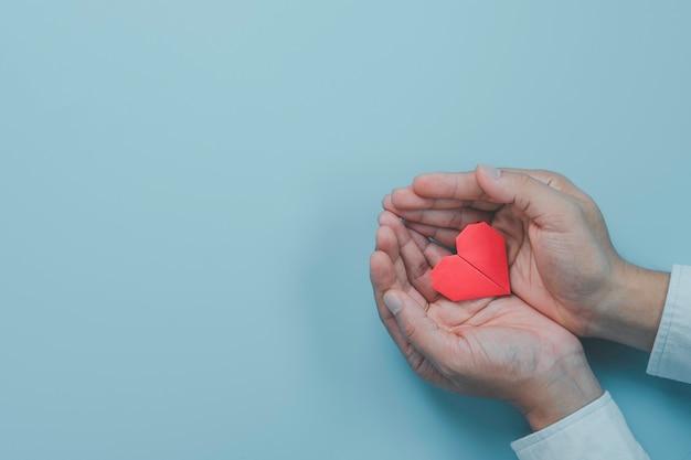 Mano di uomo d'affari che tiene carta cuore rosso con segnale d'onda del cuore su sfondo blu. è il concetto di condizione del controllo sanitario.