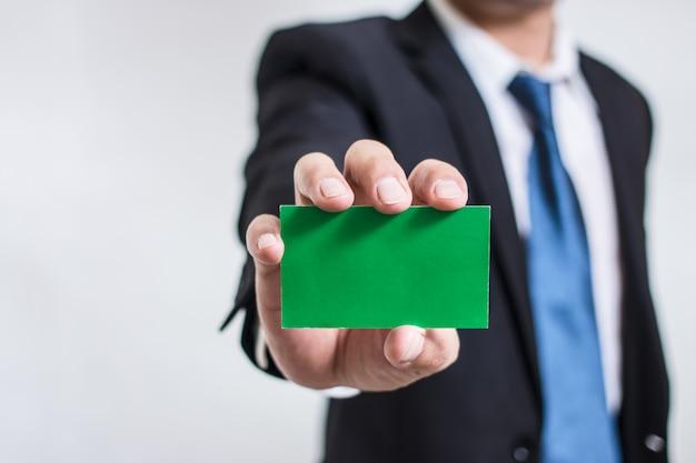 Mano dell'uomo d'affari che tiene e che mostra la carta vuota di nome aziendale