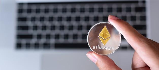 Mano dell'uomo d'affari che tiene la moneta di criptovaluta silver ethereum (eth) sulla tastiera del laptop, crypto è denaro digitale all'interno della rete blockchain, utilizza la tecnologia e lo scambio internet online.