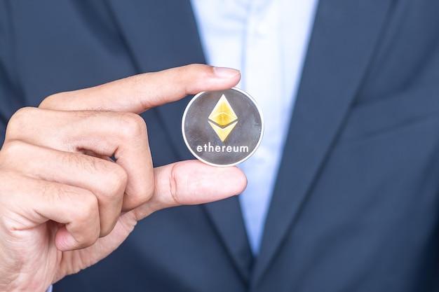 Mano dell'uomo d'affari che tiene la criptovaluta d'argento ethereum (eth), crypto è denaro digitale all'interno della rete blockchain, viene scambiata utilizzando la tecnologia e lo scambio internet online. concetto finanziario