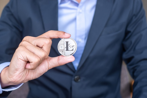 Mano dell'uomo d'affari che tiene la criptovaluta silver litecoin (ltc), crypto è denaro digitale all'interno della rete blockchain, viene scambiata utilizzando la tecnologia e lo scambio internet online. concetto finanziario