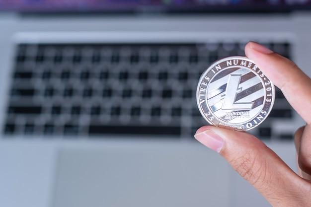 Mano dell'uomo d'affari che tiene la criptovaluta litecoin (ltc) d'argento su un laptop con tastiera, crypto è denaro digitale all'interno della rete blockchain