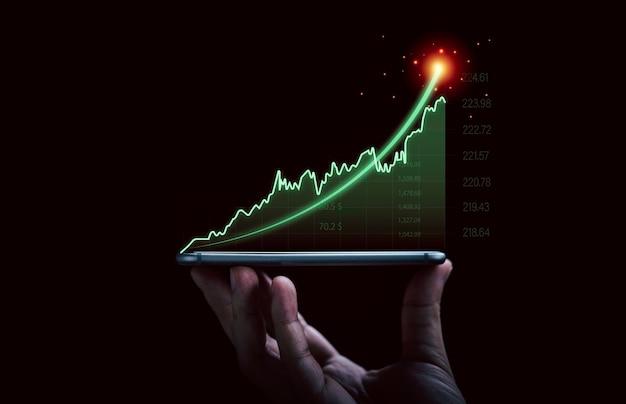 Mano dell'uomo d'affari che tiene smartphone con grafico e grafico di investimento virtuale in aumento per la tendenza dell'analisi del mercato azionario e il concetto tecnico di trader.