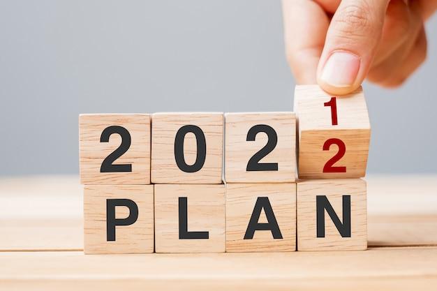 Mano dell'uomo d'affari che tiene cubo di legno e capovolgere il blocco 2021 al 2022 piano sullo sfondo del tavolo risoluzione, obiettivo, revisione, cambiamento, inizio e concetti di vacanza di capodanno