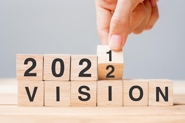 Mano dell'uomo d'affari che tiene il cubo di legno e capovolgere il blocco dal 2021 al 2022 vision sullo sfondo del tavolo. risoluzione, piano, obiettivo, missione, valore e concetti per le vacanze di capodanno