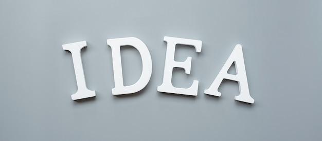 Mano dell'uomo d'affari che tiene testo di idee in legno su grigio. nuovo concetto di creatività, innovazione, immaginazione, ispirazione, soluzione, strategia e obiettivo