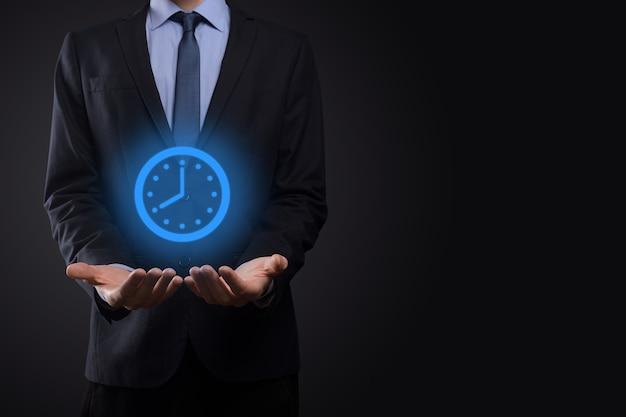 La mano dell'uomo d'affari tiene l'icona dell'orologio delle ore con la freccia.