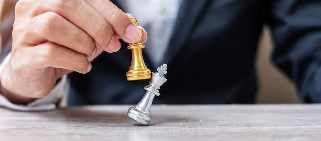 Mano di uomo d'affari in movimento figura di re degli scacchi d'oro e scacco matto enermy o avversario durante la competizione di scacchiera. strategia, successo, gestione, pianificazione aziendale, interruzione e concetto di leadership
