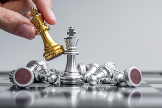 Mano di uomo d'affari in movimento figura di re degli scacchi d'oro durante la competizione di scacchiera.