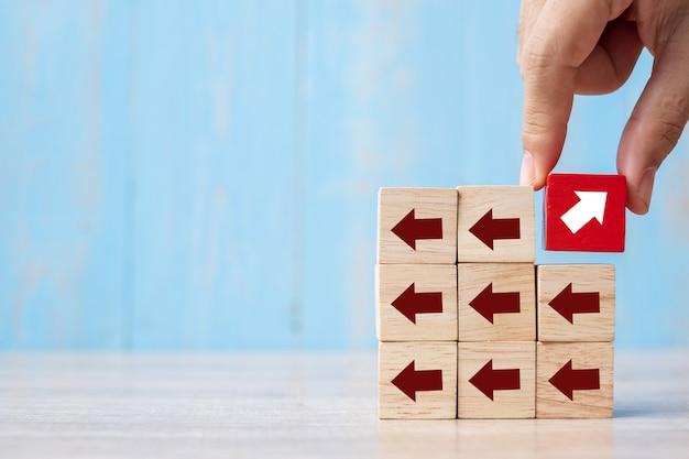Mano dell'uomo d'affari che posiziona o che tira blocco rosso con la direzione differente della freccia sul fondo della tavola. crescita del business, miglioramento, strategia, successo, diverso e unico