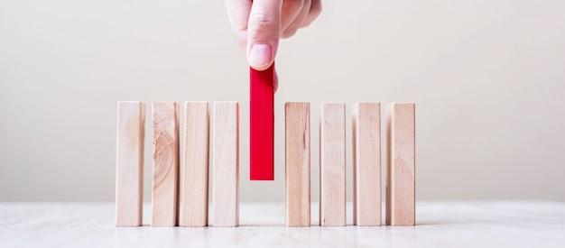 Mano dell'uomo d'affari che pone o che tira blocco di legno rosso sulla tavola. pianificazione aziendale, gestione dei rischi, soluzione, leader, strategia, concetti diversi e unici