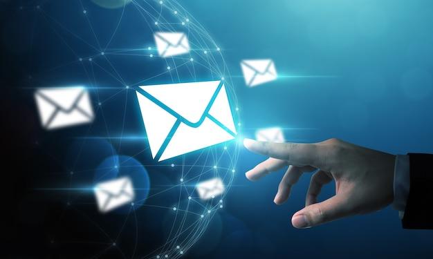 Mano di uomo d'affari che indica icona enverlope di posta elettronica