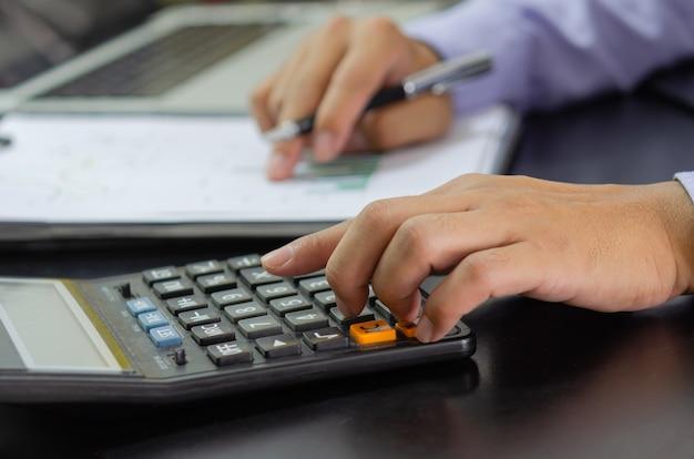 Mano dell'uomo d'affari che preme un calcolatore concetto di affari, finanza, imposta e investimento.