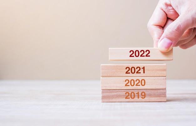 Mano dell'uomo d'affari che tira 2022 blocchi di costruzione di legno sul fondo della tavola. pianificazione aziendale, gestione del rischio, risoluzione, strategia, soluzione, obiettivo, capodanno capodanno e concetti di felice vacanza