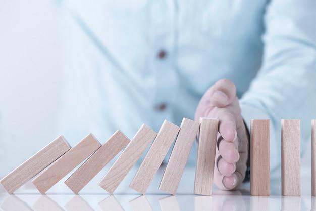 Mano dell'uomo d'affari che ferma l'effetto domino per gestione e soluzione, strategia di concetto e intervento riuscito