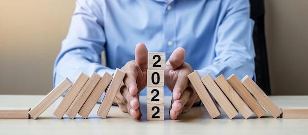 Mano dell'uomo d'affari che interrompe la caduta di 2022 blocchi di legno. affari, gestione del rischio, assicurazione, risoluzione, strategia, soluzione, obiettivo, anno nuovo nuovo te e concetti di felice vacanza