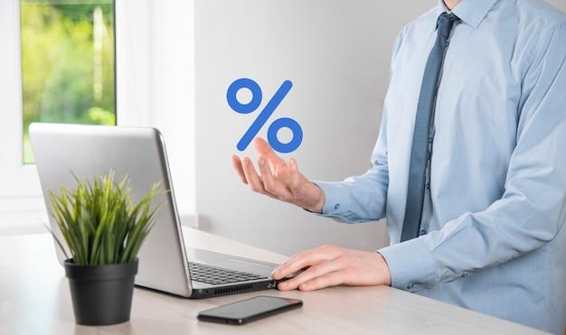 La mano dell'uomo d'affari prende un'icona del simbolo di percentuale. tasso di interesse finanziario e concetto di tassi ipotecari.