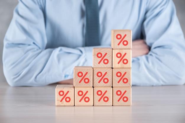 La mano dell'uomo d'affari prende un blocco cubo di legno raffigurante, mostrato l'icona del simbolo di percentuale. concetto di tassi di interesse finanziario e ipotecario.