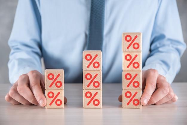 La mano dell'uomo d'affari prende un blocco di cubo di legno raffigurante, mostrato l'icona del simbolo di percentuale. concetto di tassi di interesse finanziario e ipotecario.