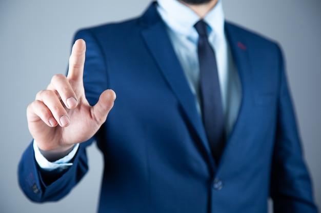 Mano dell'uomo d'affari che tocca il concetto moderno del fondo dello schermo virtuale può mettere il vostro testo al dito