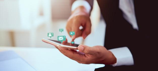 Mano dell'uomo d'affari facendo uso dei media sociali dell'icona di tecnologia di manifestazione e dello smartphone. concetto di social network.