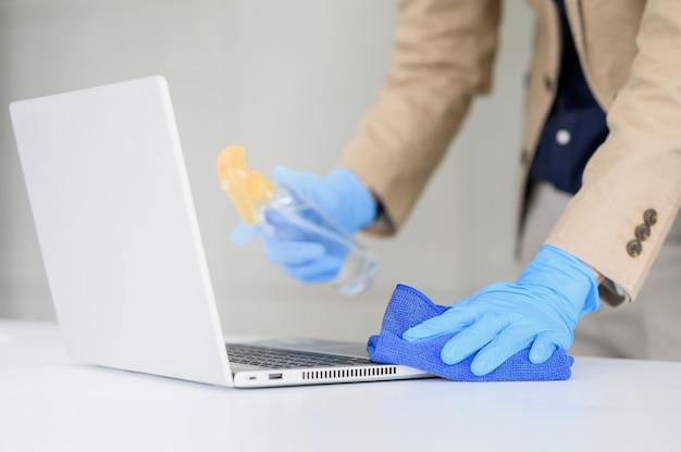 Guanto di usura della mano dell'uomo d'affari facendo uso del panno del microfiber per pulire computer portatile