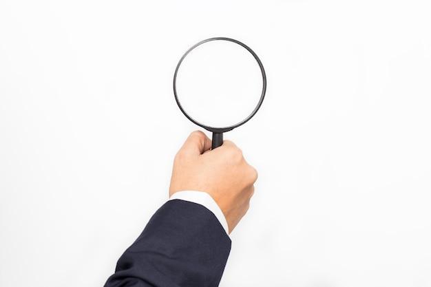 Mano dell'uomo d'affari con la lente d'ingrandimento isolata su bianco