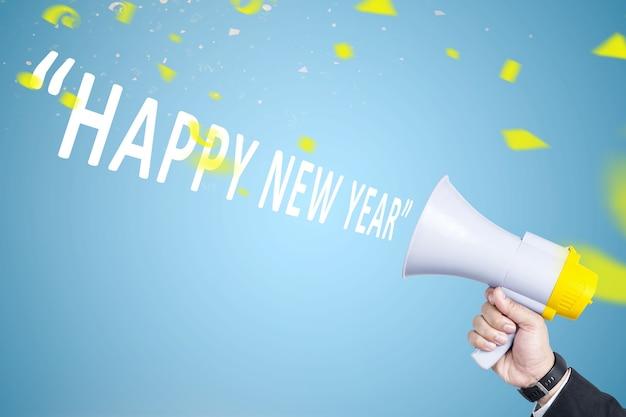 Mano di uomo d'affari con un megafono annuncia il felice anno nuovo. felice anno nuovo 2021