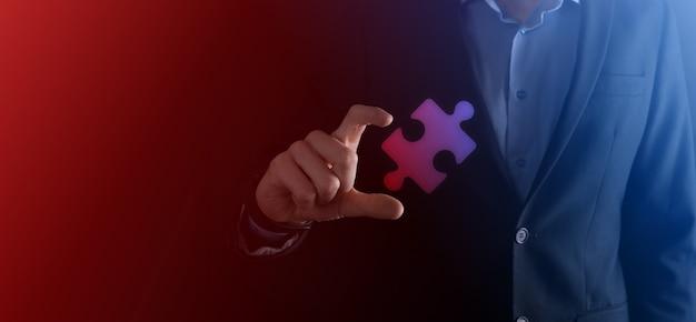 Mani dell'uomo d'affari che collegano i pezzi del puzzle che rappresentano la fusione di due società o joint venture, partnership, fusioni e concetto di acquisizione.